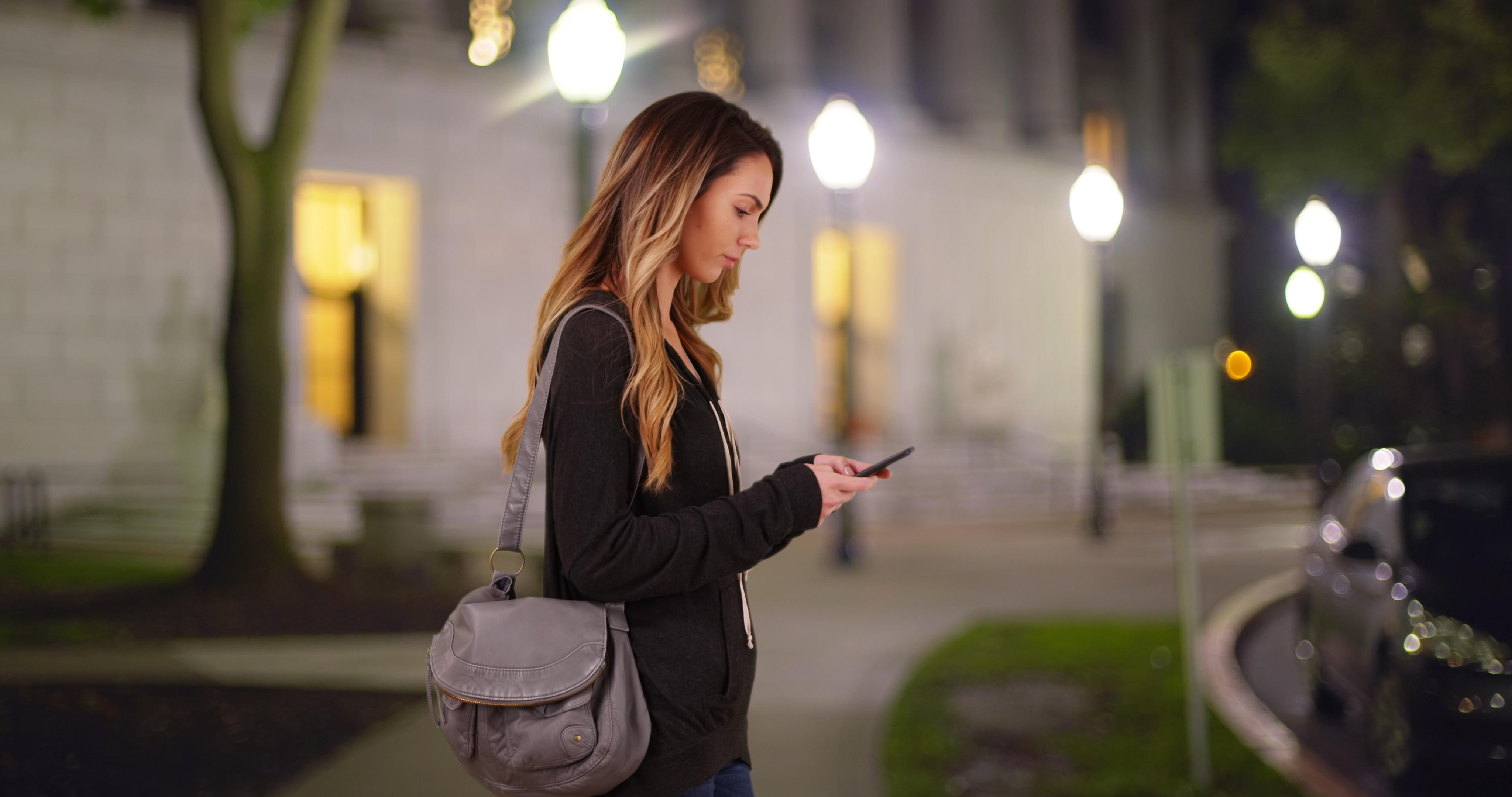 Girl walking on campus checking her phone